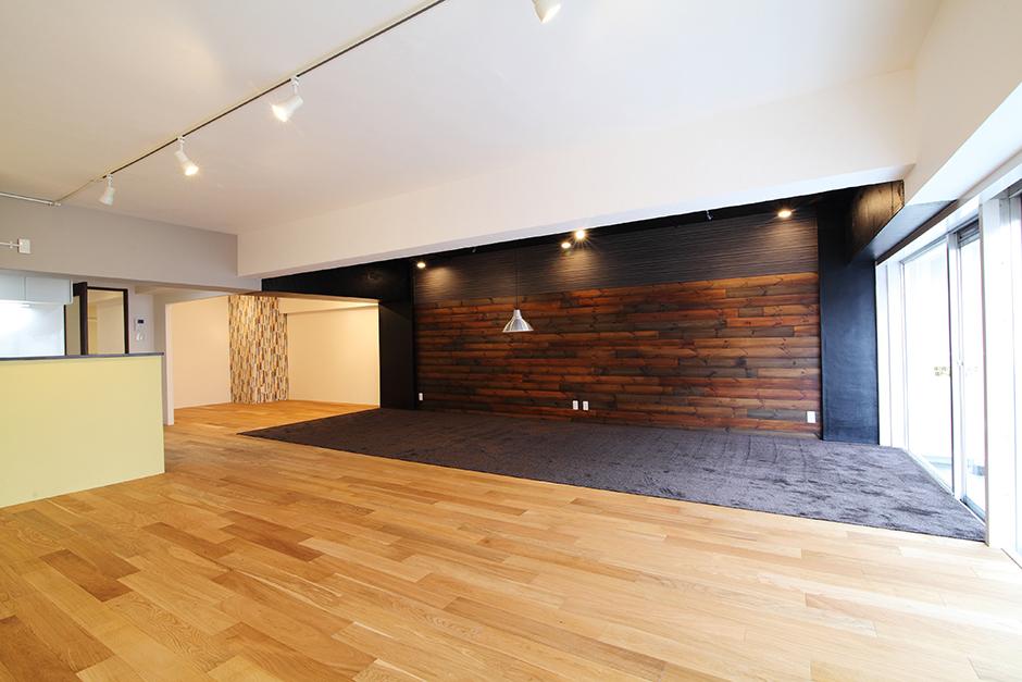 施工後:全体:白い塗り壁をアクセントにした明るいリビングと、むき出しのコンクリート天井を黒く塗装したリラックススペース。大きな空間を色で緩やかに区切る。