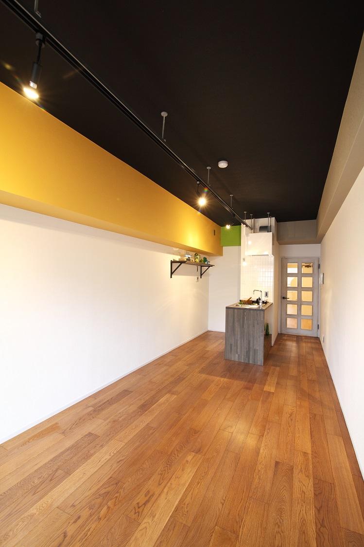 完成:洋室:天井は黒いクロスを貼り、あえて天井を低く見せる。間接照明と無垢フローリングの仕上げでカフェ風に。