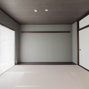 天井は黒い板目、壁はグレー色、畳はカラー畳で桜色。プリーツスクリーンはさりげなく畳に合わせており、柔らかい光がきれい。