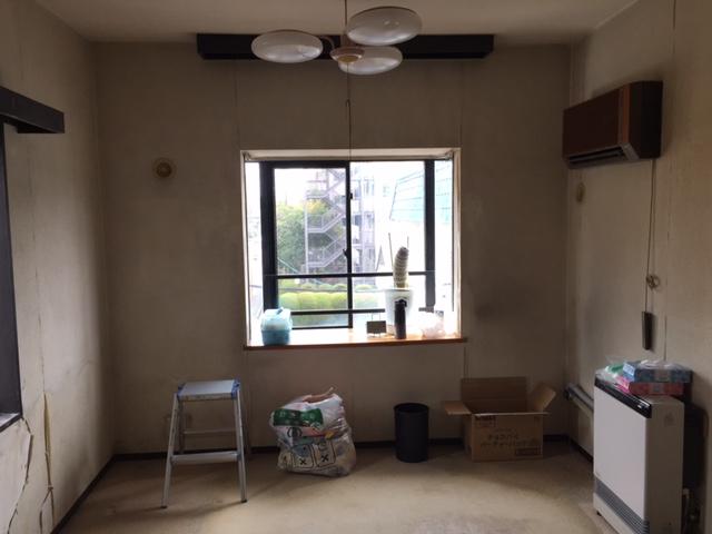 床のカーペットには様々な汚れ染みが。窓が小さいため暗い印象。